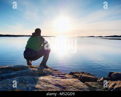 Lonely man hiker sits alone on the rocky  coast and  enjoying sunset. View over rocky cliff to free ocean - Stock Photo