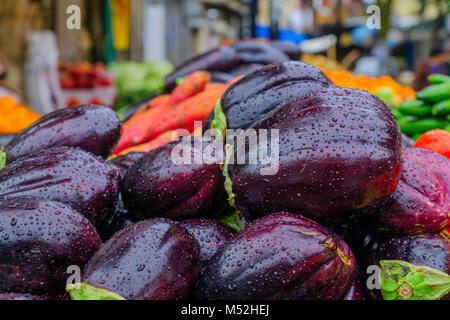 Eggplants displayed for sale in the market, on a rainy day - Stock Photo