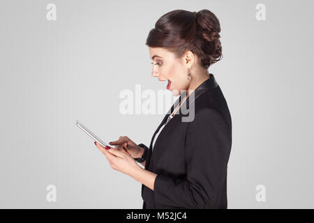 Profile side businesswoman , holding tablet, open mouth, shocked. Studio shot, indoor. Isolated on grey background - Stock Photo