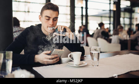 Young man using electronic cigarette to smoke in closed public space.Satisfied e- cigarette user in cafe.Smoking ban alternative,nicotine addiction,qu