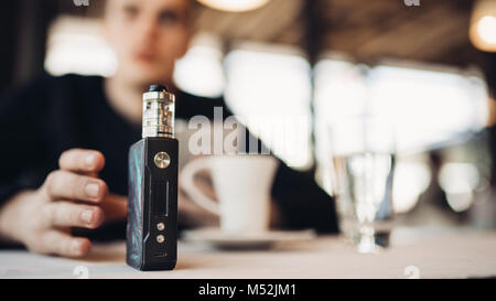 Using electronic cigarette to smoke in public places.Smoke restriction,smoking ban.Using vaping device with flavoured - Stock Photo