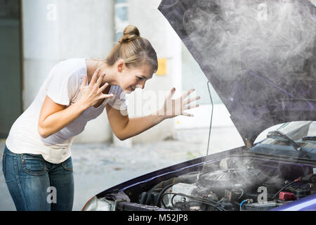 Frustrated Young Woman Looking Under The Hood Of Breakdown Car - Stock Photo