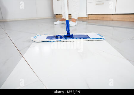 Low Section Of Person Wiping Floor With Mop In Kitchen Room - Stock Photo