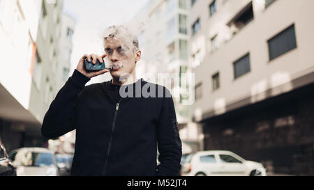 Young man using electronic cigarette to smoke in public places.Smoke restriction,smoking ban.Using vaping device - Stock Photo