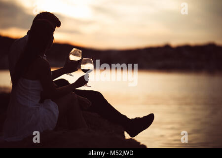 Romantic couple drinking wine at sunset at a pier on a seaside.Romance.Two people having a romantic evening with - Stock Photo