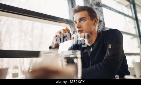 Young man vaping in closed public space.Smoking electronic cigarette in cafe.Nicotine addiction.Way to quit smoking,old - Stock Photo