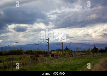 Stunning New Zealand landscape with Mount Ngauruhoe covered in snow and a cloudy dramatic sky. - Stock Photo
