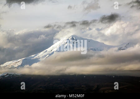 Mount Ngauruhoe with snow on top, and dramatic stormy clouds - Stock Photo