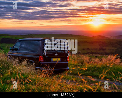 VW California camper van parked up for the night at a free glamping location the occupants enjoying the lovely sunset - Stock Photo