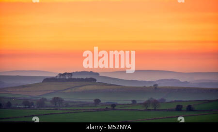 Sunset over Minning Low hill Historic England monument with a chambered tomb & two bowl barrows viewed from Harborough - Stock Photo