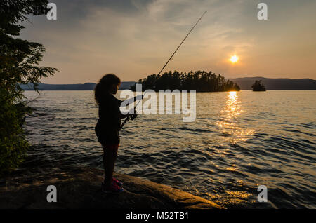 Young Hispanic girl fishes on a rock at Lake George in New York near the Adirondack Mountains as the setting sun casts a golden glow over her face. Stock Photo