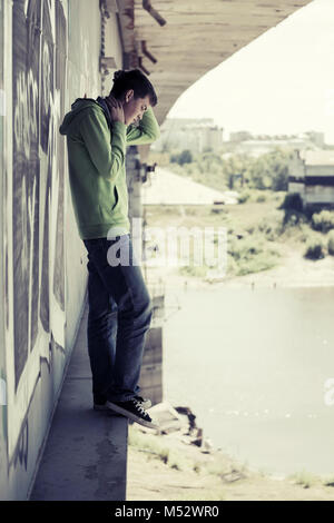 Young man in depression standing on the river bridge - Stock Photo