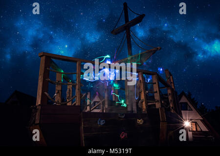 Colorful ghostly lighttrails on a deck of a pirate ship - Stock Photo