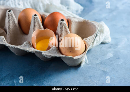 Fresh eggs, whole and broken, in a paper packaging on a concrete background. Fresh ingredients for Easter cooking. - Stock Photo
