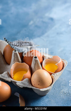 Raw hen eggs in craft carton pack. Close-up with copy space. Broken shell with visible yolk. - Stock Photo