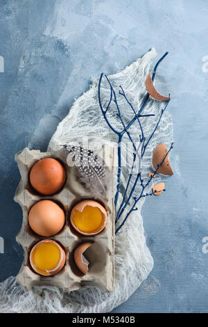 Easter decorations concept with fresh eggs in a carton, tree branches and cloth runner on a concrete background. - Stock Photo