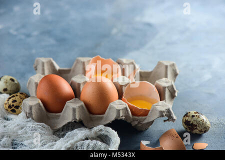 Fresh quail and chicken eggs, whole and broken, in a paper packaging on a concrete background. Raw ingredients for - Stock Photo