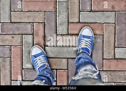 Legs in blue sneakers - Stock Photo