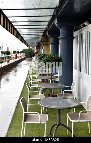A row or line of tables and chairs on the riverbank of the thames in central london outside of a restaurant or cafe - Stock Photo