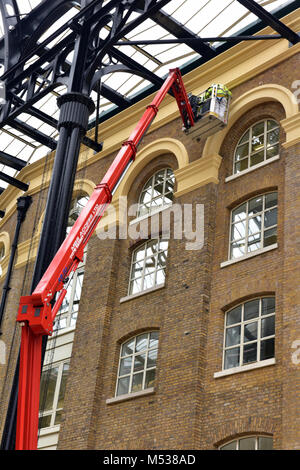 a cherry picker or mobile elevated work platform being used to gain access to a high window on a wall for maintenance - Stock Photo