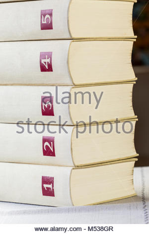 Texture of two leather bound gilt tooled vintage books with decorative patterns on the spines in front of the balance - Stock Photo