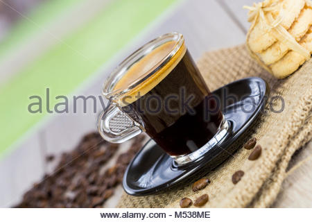 Strong mug of freshly brewed espresso coffee with coffee beans with a dainty pile of crunchy cookies tied together - Stock Photo