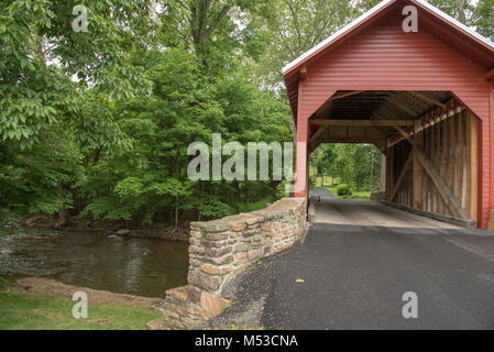 The Roddy Road red covered bridge carries local trafffic over a stream. It is located near Thurmont in Frederick - Stock Photo