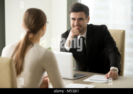 Smiling bank employee talking with female client - Stock Photo