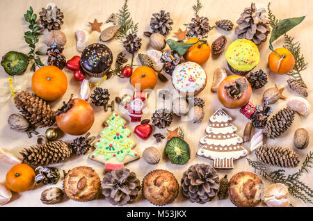 Christmas cookies,toy Santa Claus,fruits,nuts, pine cones with chocolate sweets on a plywood table - Stock Photo