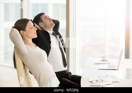Young business leaders practice yoga at workplace - Stock Photo
