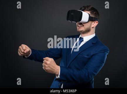 Excited business man in suit looking through virtual reality headset and acting like he is driving