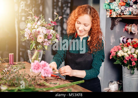 Young woman selecting flowers at market - Stock Photo