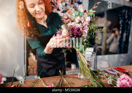 female putting winsome flowers in vase in florist's shop - Stock Photo