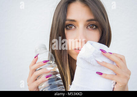 Portrait of beautiful woman drinking water and wiping her sweat after exercising - Stock Photo