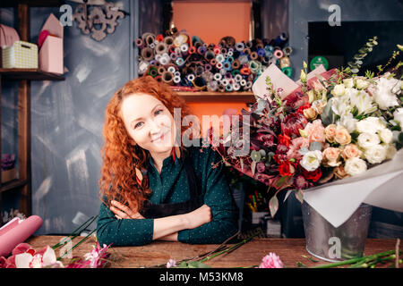 florist-designer with red hair and green eyes working at florist's shop - Stock Photo