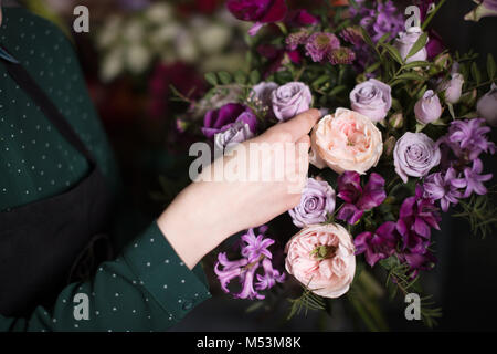 young vendor touching beautiful roses at shop - Stock Photo
