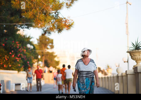 Elegant mature woman walking on promenade during summer sunset in park. Portrait of elederly woman of 65 years in - Stock Photo