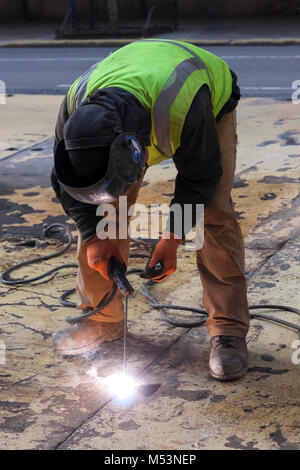 A worker welding a steel plate on a New York City street. - Stock Photo