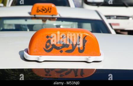 Taxi signs in English and Arabic in the Arabian Gulf - Stock Photo