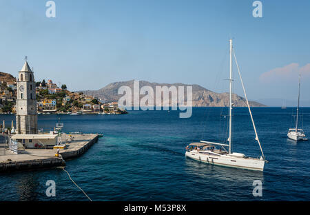 The clock tower and the entrance to the port of Symi, (or Simi), a tiny, quite and picturesque island of Dodecanese, - Stock Photo