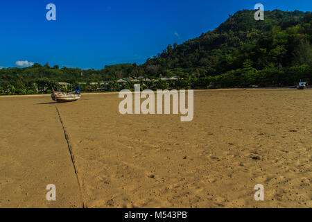 Traditional Thai wooden longtail boats (Rua Hang Yao) moored on the sand at small pier with blue sky and small island - Stock Photo