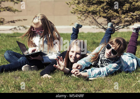 Teenage school girls lying on the grass in campus - Stock Photo