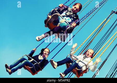 Teen girls on the chain swing carousel - Stock Photo