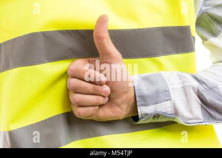 Construction builder showing like gesture behind back on reflective vest background - Stock Photo
