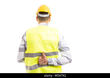Constructor or builder showing like thumbs-up gesture behind back isolated on white studio background - Stock Photo