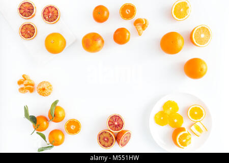 Composition of blood oranges, oranges and  clementines whole, halved, peeled, and sliced arranged on marble board, - Stock Photo