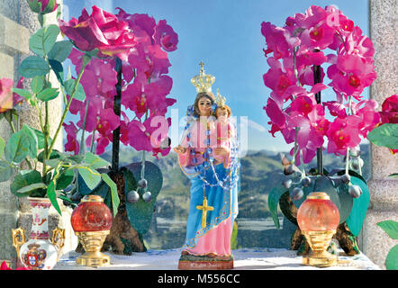 Colorful village altar in glass vitrine with Madonna and pink flowers with mountain landscape in the background - Stock Photo