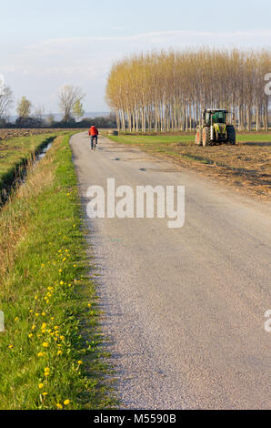 Country road in an early spring afternoon with a cyclist in the background and a tractor at work in the field alongside - Stock Photo