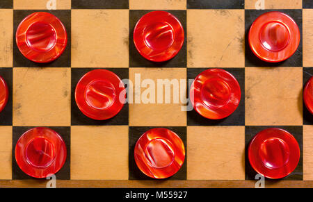 A few wooden pearly red pieces on a checkerboard - Stock Photo