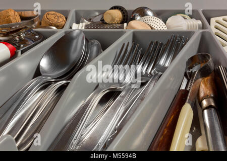 Close-up of the contents of a kitchen drawer full of cutlery and utensils - Stock Photo